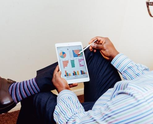 image of a man looking at statistics on an ipad